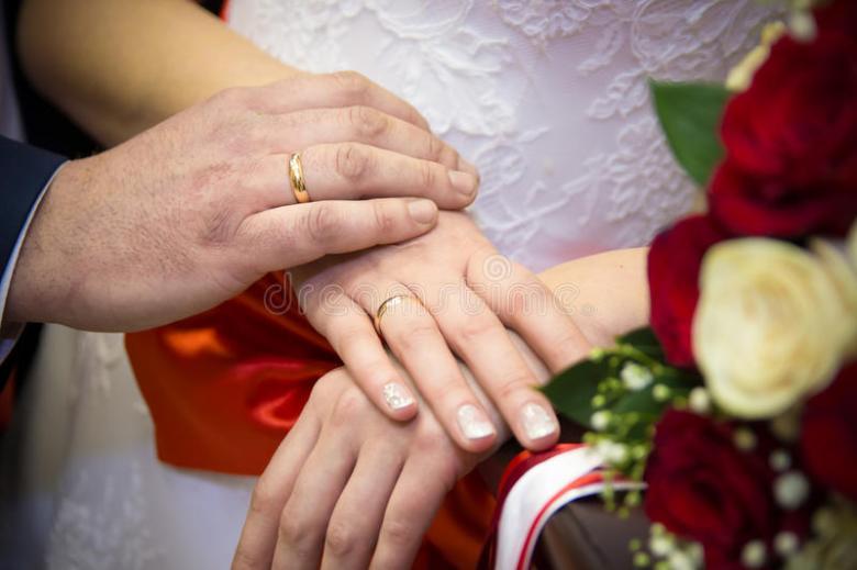 mãos-e-noivo-da-noiva-dos-anéis-no-fundo-de-um-ramalhete-do-casamento-90499113